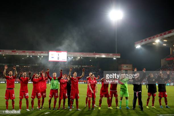 Union Berlin players celebrate to their fans following their team's victory in the Bundesliga match between 1 FC Union Berlin and Hertha BSC at...