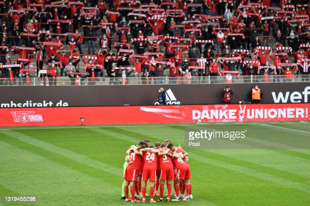 Union Berlin players huddle as fans hold up scarves prior to the Bundesliga match between 1. FC Union Berlin and RB Leipzig at Stadion An der Alten...