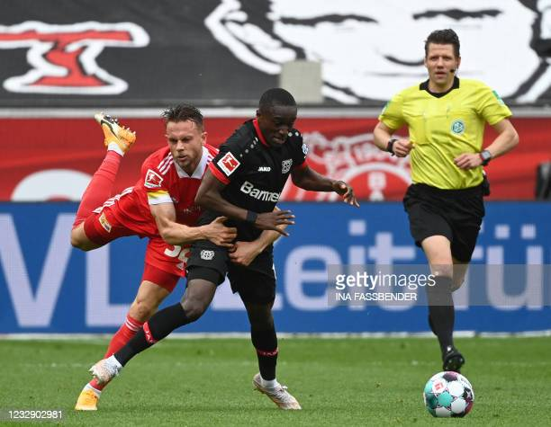 Union Berlin's Danish forward Marcus Ingvartsen and Leverkusen's French forward Moussa Diaby vie for the ball during the German first division...