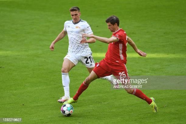Union Berlin's German midfielder Grischa Proemel and Bayern Munich's German forward Thomas Mueller vie for the ball during the German first division...