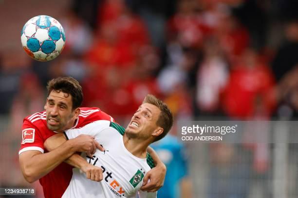 Union Berlin's German midfielder Rani Khedira and Moenchengladbach's German forward Patrick Herrmann vie for the ball during the German first...