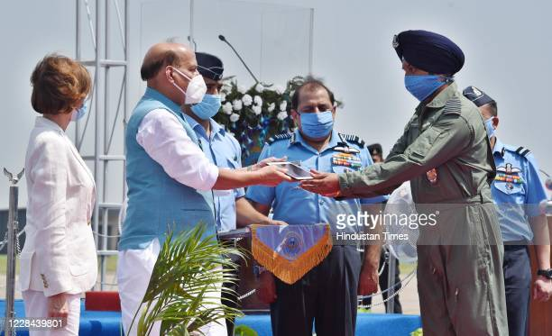 Union Defence Minister Rajnath Singh presents a memento to an IAF officer during Rafales induction ceremony on September 10, 2020 in Ambala, India....