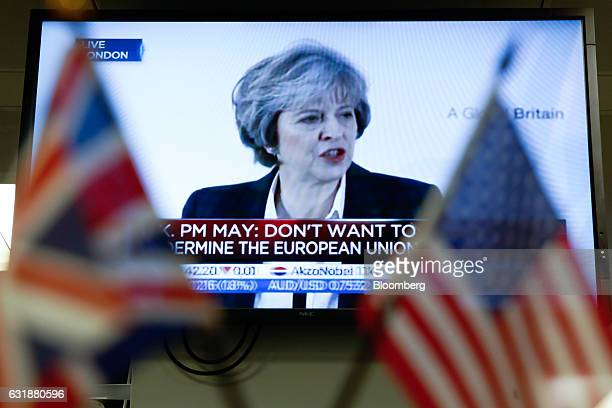 A Union Flag also known as a Union Jack left and a US flag sit in front of a television screen displaying a news channel showing UK Prime Minister...