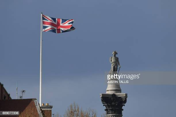 A Union flag flaps in the wind on a building near to Nelson's Column in Trafalgar Square in central London on March 28 2017 British Prime Minister...