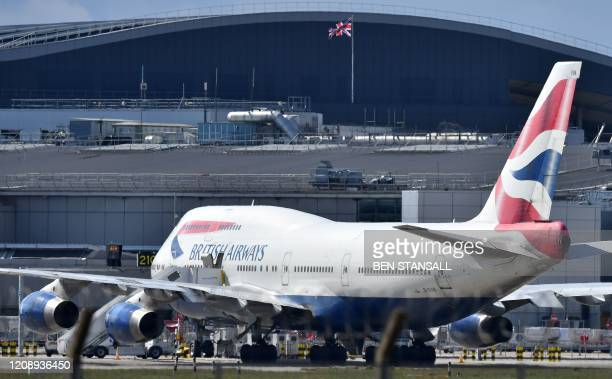 Union flag flies above a hangar as a British Airways operated Airbus A747 passenger jet is moved by an aircraft tractor at Heathrow Airport, west of...