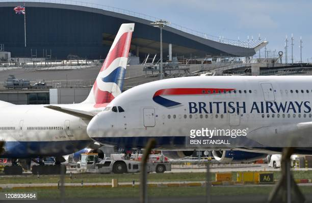 A Union flag flies above a hangar as a British Airways operated Airbus A380 passenger jet is moved by an aircraft tractor at Heathrow Airport west of...