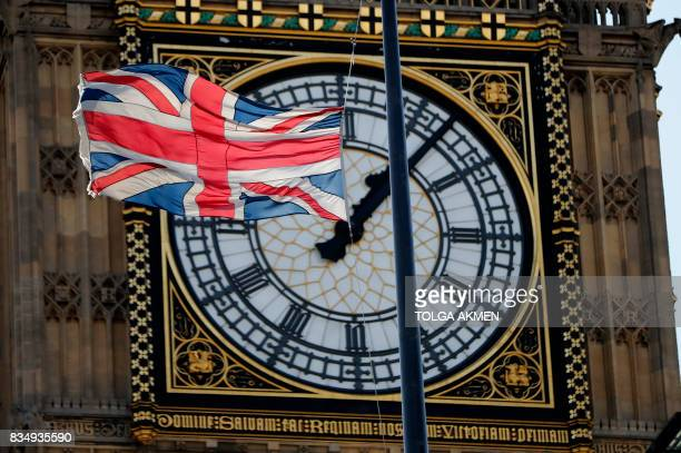 A Union flag flies at halfmast from the roof of a building in front of a face of the Great Clock of the Palace of Westminster's Elizabeth Tower more...