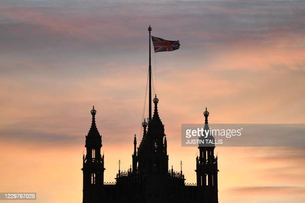 Union flag flies atop the the Victoria Tower at Palace of Westminster, comprising both houses of parliament, the House of Commons and the House of...