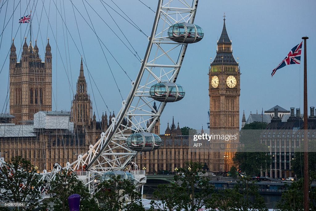 A Union flag flies beside the London Eye in front of the Queen Elizabeth Tower (Big Ben) and The Houses of Parliament in London on June 24, 2016. Britain's economy was plunged into a dizzying unknown on Friday as the country lurched towards the EU exit, with the world economy bracing for a hit on growth and unemployment. / AFP / POOL / ROB