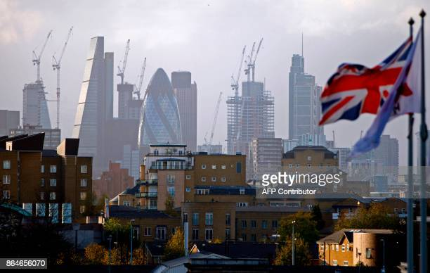 A Union flag flies from a pole as construction cranes stand near skyscrapers in the City of London including the Heron Tower Tower 42 30 St Mary Axe...