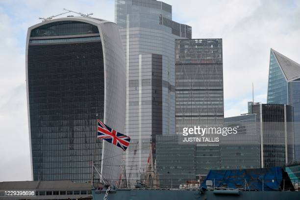 Union Flag flies from HMS Belfast moored on the River Thames in the shadow of the office buildings of the City of London in London on November 1,...
