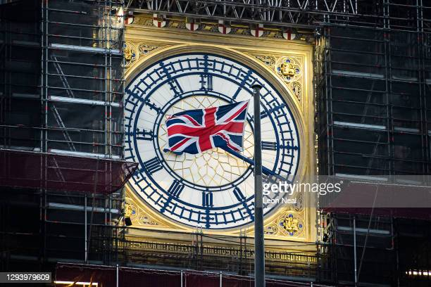 Union flag flies in front of the clock face of Elizabeth Tower, commonly known as Big Ben, just after the sun rises on January 01, 2021 in London,...