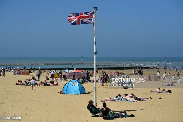 Union flag flutters in the breeze as sunbathers take advantage of the fine weather on the beach on the coast at Margate, east of London on May 31 as...