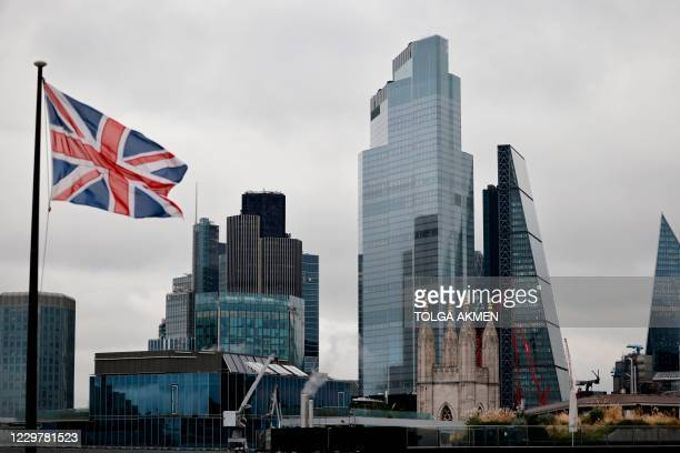 Union Flag flutters in the wind near office builings in the City of London in London on November 25, 2020. - Britain's economy is set to shrink 11.3...