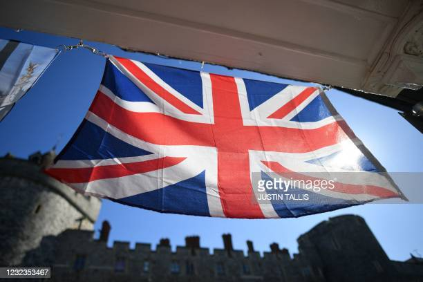 Union Flag hangs in the doorway opposite Windsor Castle, in Windsor, west of London, on April 17, 2021 ahead of the funeral of Britain's Prince...