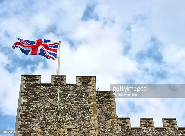 Union flag previously called the union jack fluttering in the wind on top of a tower at Dover Castle