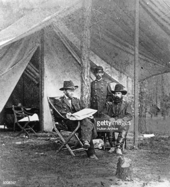 Union General Ulysses S Grant sitting with two men in front of a tent at camp during the US Civil War