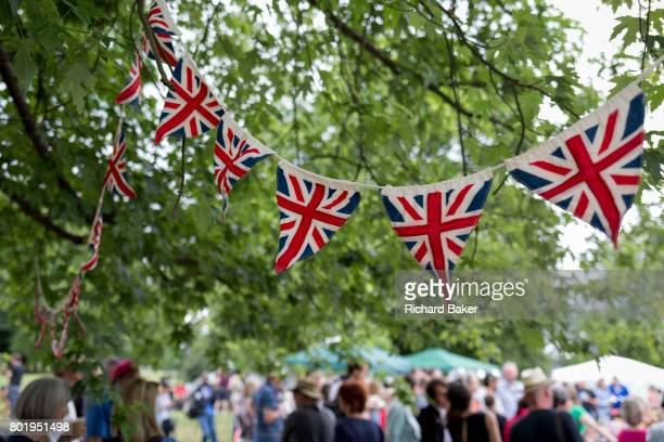 Union Jack bunting hangs over a British summer fete bringing the local community together and to celebrate their important public space, on 24th June...