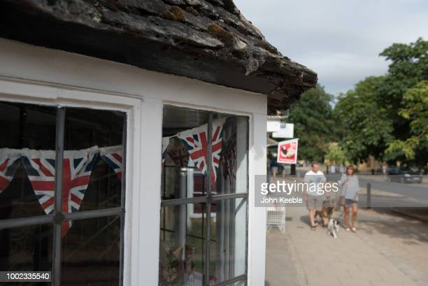 Union Jack bunting is seen hanging in an old leaded shop window as a couple walk their dogs in the Cotswolds on July 10 2018 in Broadway England