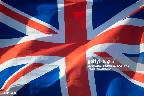 union jack flag fluttering in the wind - union jack stock pictures, royalty-free photos & images