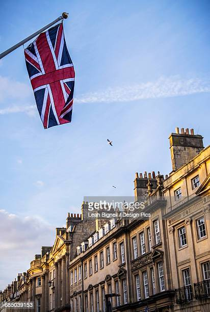 a union jack flag flying in the streets of bath - bath england stock pictures, royalty-free photos & images