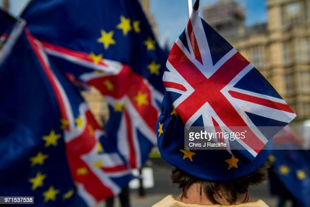 Union Jack flag is seen on top of a woman's EU hat as antiBrexit demonstrators gather outside the Houses of Parliament on June 11 2018 in London...