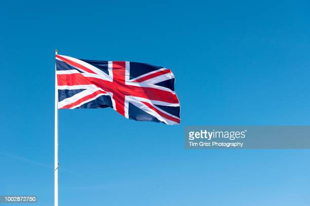 union jack flag of great britain against a blue sky - union jack stock photos and pictures