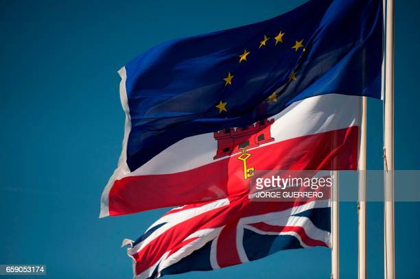 A Union Jack flag the flag of Gibraltar and the European Union flag fly in Gibraltar on March 28 2017 Gibraltar the British overseas territory on...