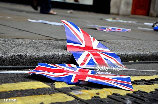 Union Jack flags are seen lying abandoned as rubbish in the gutter after a street party celebration. Possibly a symbol of the Olympic Legacy!