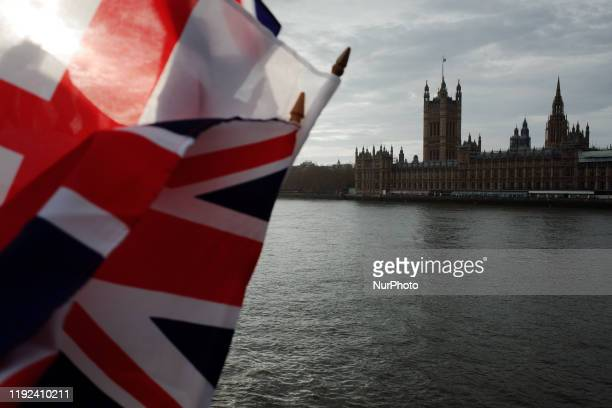 Union Jack flags flutter in the breeze at a souvenir stall across the River Thames from the Houses of Parliament in London England on January 7 2020...