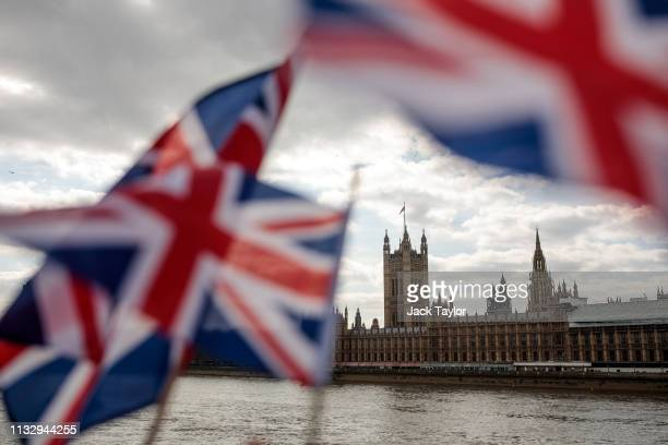 Union Jack flags flutter in the wind in front of the Houses of Parliament in Westminster on March 26 2019 in London England British Prime Minister...