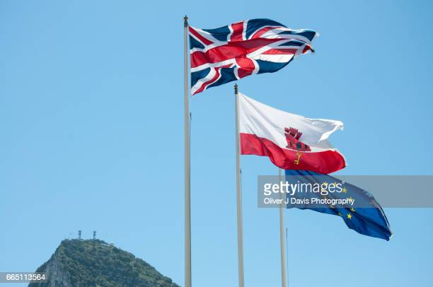 union jack, gibraltar and eu flags at gibraltar's border with spain, with the rock of gibraltar behind. - gibraltar stock pictures, royalty-free photos & images