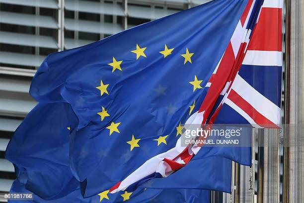 A Union Jack hangs down next to European Union flags fluttering in front of the European Commission building as British Prime Minister May is due to...