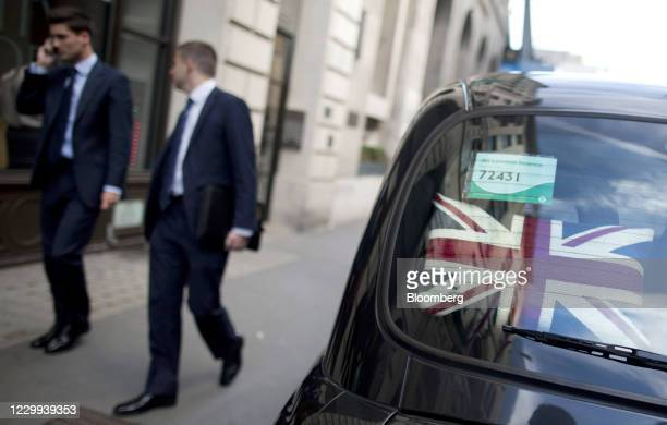 Union Jack pillow sits on the parcel shelf of a London taxi cab as businessmen walk past in London, U.K., on Friday, Aug. 17, 2012. European Union...