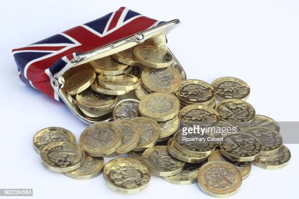 union jack purse with one pound coins spilling out. - clutch bag stock pictures, royalty-free photos & images
