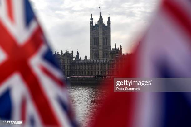 Union Jacks flap in the wind in front of the Houses of Parliament on October 23 2019 in London England MPs voted against the government rushing...