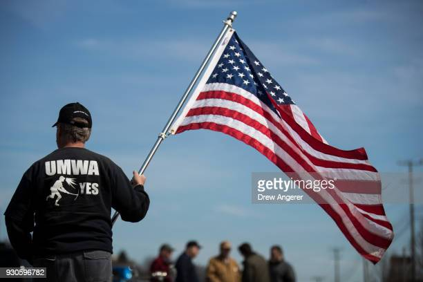 A union member holds an American flag before the start of a campaign rally with United Mine Workers of America at the Greene County Fairgrounds March...