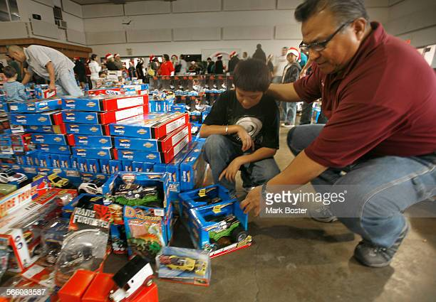 CA DECEMBER 21 2009 Union member Steve Roldan helps one of the children to pick out a gift at the toy giveaway at the International Longshore and...
