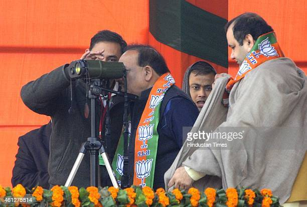 Union Minister of Science and Technology Harshvardhan looks through the binoculars as Member of Parliament Maheish Girri and Parvesh Verma wait for...