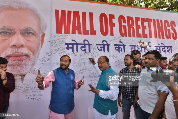 Union Ministers Prakash Javadekar and Vijay Goel gestures towards BJP supporters during an event Wall of Greetings organised by BJP at Rajiv Chowk on...