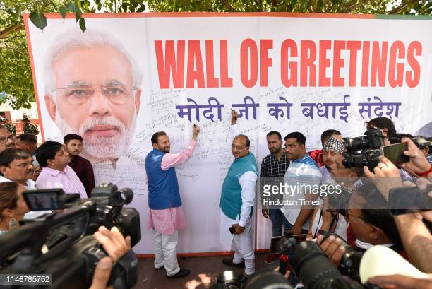 Union Ministers Prakash Javadekar and Vijay Goel seen writing the greetings during an event Wall of Greetings organised by BJP at Rajiv Chowk on May...