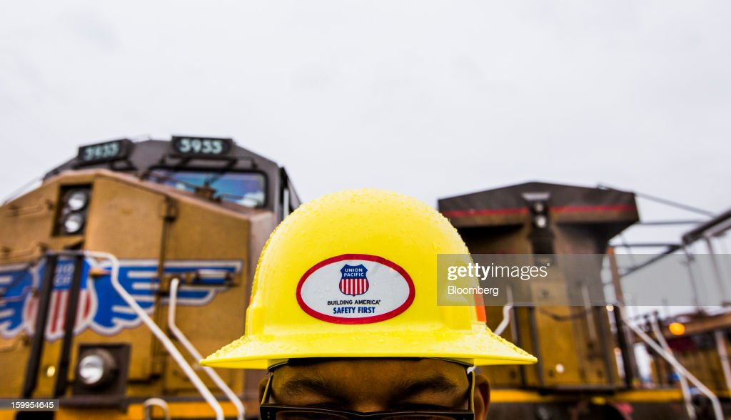 Union Pacific Corp. employee Jeff Smith wears a safety hat bearing the company's logo as he surveys rail cars at its facility at the Port of Oakland in Oakland, California, U.S., on Wednesday, Jan. 23, 2013. Union Pacific Corp., the largest U.S. railroad by sales, is scheduled to report fourth-quarter earnings results on Jan. 24 before the opening of U.S. financial markets. Photographer: Ken James/Bloomberg via Getty Images