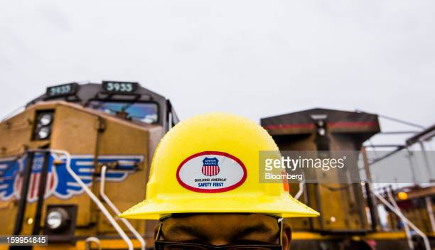 Union Pacific Corp employee Jeff Smith wears a safety hat bearing the company's logo as he surveys rail cars at its facility at the Port of Oakland...