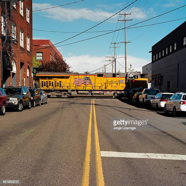 CONTENT] Union Pacific train engine moving across city street between industrial buildings Vanishing point perspective Portland Oregon Hasselblad...