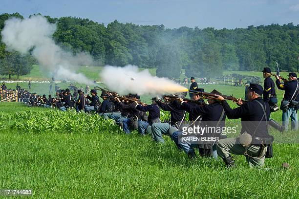 Union soldiers fire a volley at Confederate troops during reenactment of the Battle of Gettysburg on June 28 2013 at the start of the 150th...