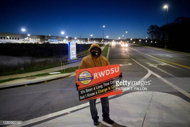 Union supporter stands before sunrise outside the Amazon.com, Inc. BHM1 fulfillment center on March 29, 2021 in Bessemer, Alabama. - Votes are set to...