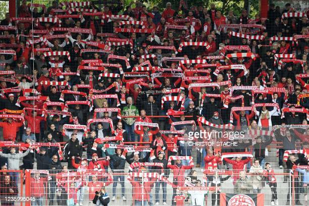 Union supporters cheer with their fan scarves prior the German first division Bundesliga match between Union Berlin and VfL Wolfsburg in the stadium...