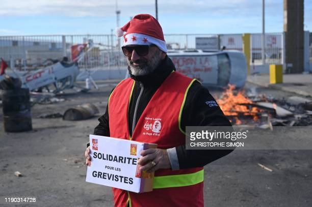 A CGT unionist holds a box for strike fund donations during a Christmas lunch on December 24 2019 at the autonomous port of Marseille on the 20th day...