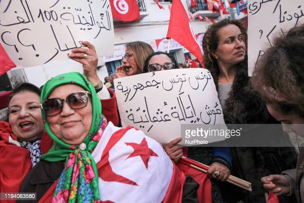 Unionists dressed in Tunisian flag while shouting slogans against the government raise Tunisian flags and a placard which reads 'Tunisia is a...