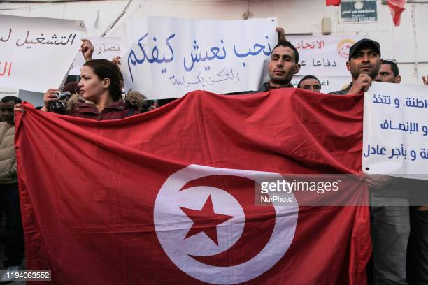 Unionists hold a giant flag of Tunisia and raise a placard which reads 'I want to live like you but with dignity' in Arabic as they gather outside...